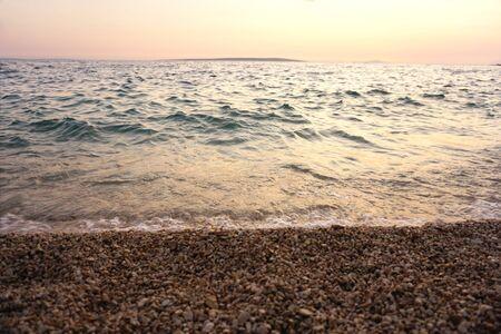 Sea tide and turbulent wavy sea on a pebble beach at sunset