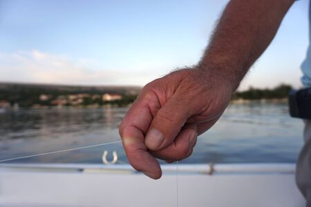 Male hand holds the fishing thread. A man standing in a boat in a sea lagoon in front of seacoast and fishing saltwater fish in the traditional way with nylon line, on the evening