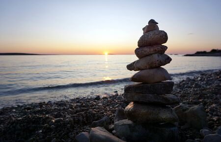 Background with tower of stacking stones on the empty pebble beach at summer sunset, with copy space