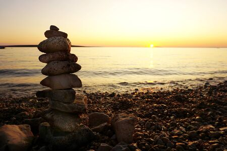 Background with stone is stacked in a vertical line on the beautiful pebble beach at sunset, with copy space
