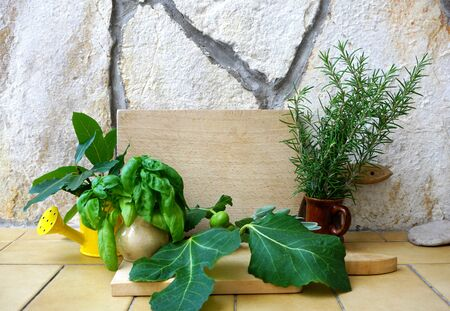 Aromatic culinary herbs collection. Mediterranean spices, rosemary, basil, laurel leaves and figs on a rustic stone background and with a wooden kitchen board in the middle with copy space