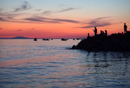 Blue hour pastel background with silhouette of young and old people fishing on the peninsula in the beautiful summer sunset in blue and purple color tone