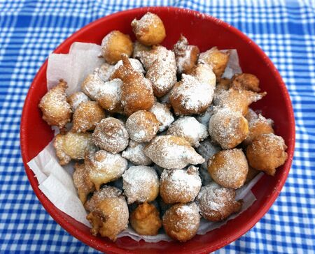 Red bowl full of homemade fritters or fritule powdered with icing sugar on the vintage kitchen dish towel. Traditional Croatian homemade dessert fritule Stockfoto