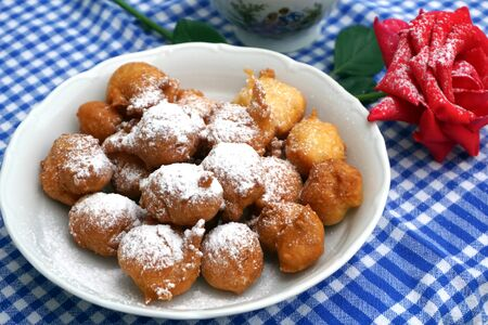 Sweet homemade fritter balls powdered with icing sugar and served on decorated table