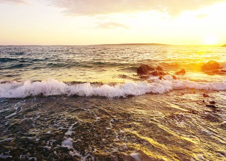 Seascape background with tide and waves on the seacoast in the evening lit by sunlight during sunset