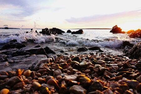 Sea wave in the shallow water and a sunlit pebble beach at sunset 스톡 콘텐츠