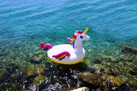Summer, holiday and vacation background with copy space. Inflatable unicorn in the shallow blue sea water on the sunny summer day