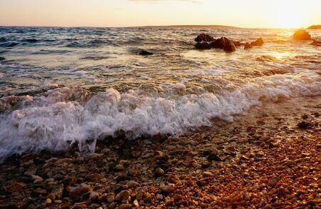 Sunset sea background with sea water floods the seacoast and creates a wave with white foam
