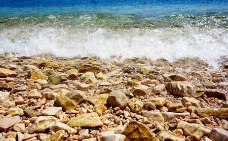 Dynamic tidal white wave splashing on the pebbles sea coast and beach with pebbles on a sunny day