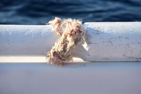 Broken rope tied in a knot around part of the old wooden paddle on the white boat with blue sea surface in the background and copy space