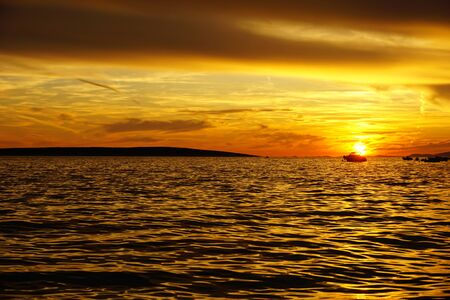 Beautiful nature background with sunset in orange, yellow, black and beige color tones of the sea and sky and with black silhouettes of boats