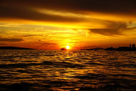 Sky with dramatic red, orange and copper color tone clouds at sunset, dusk nature background with silhouette of boats and people. Colorful and shiny nature background