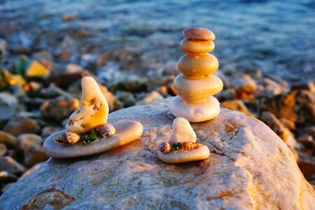 Craft souvenirs from pebbles. Sunset reflection on the sea beach with pebble art, small stacking stones and decorative boats made from small stones and decorated with seashells