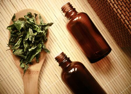 Raw organic sun dried herb on wooden background with little drop bottles prepared to make essential oil or liquid