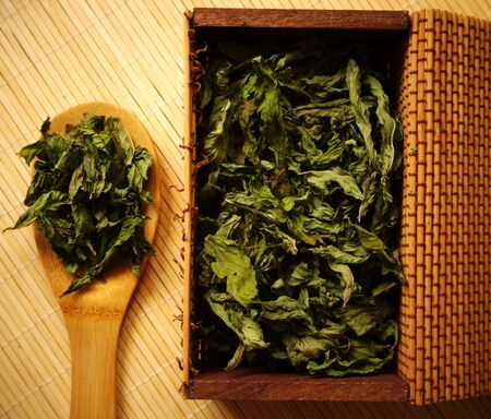 Peppermint dried green leaves in the wooden bamboo spoon and box, prepared for making fresh and healthy tea from organic herb