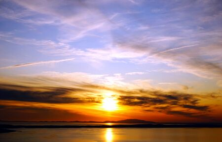 Cloudscape and vivid color sunset above shiny sea surface and dramatic sky
