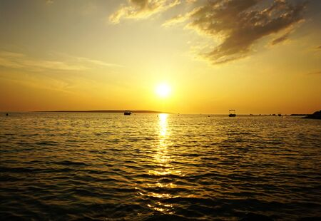 Nature background with beautiful sunset with shiny yellow sun ball in the cloudy sky and above wavy sea surface Stockfoto