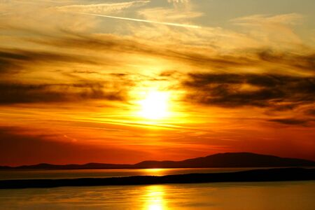 Beautiful dusk and red sunset on burning dramatic sky and sun reflection on the sea surface Stockfoto