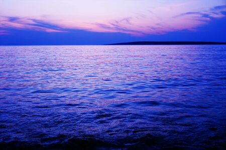 Calming background with purple and blue color tone sea water surface and horizon line at the sundown Stockfoto