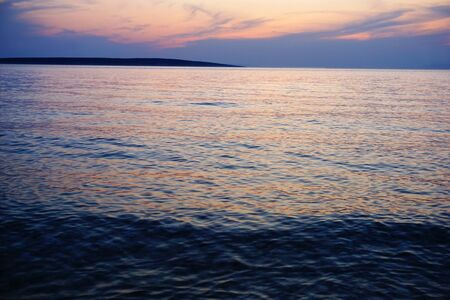 Water background with flood tide on the sea at the beautiful dusk sunset with dramatic sky on the horizon
