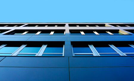 Modern architecture building detail. Bottom view of a modern facade with glass windows