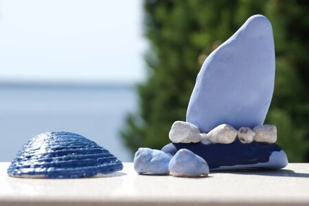 Background with do it yourself souvenirs, colored boat made of pebble and sea shells in front of sea and treetop