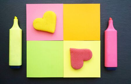 Multicolored vivid sticky note in square shaped with marker pens by side on the black board background decorated with two hearts