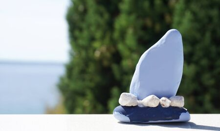 Blue craft boat made from small stone and seashells with blurred nature background of green cypress and sea