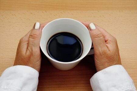 Hands of a middle aged Caucasian woman they hold a cup of black coffee, flat lay on the wooden background with free copy space