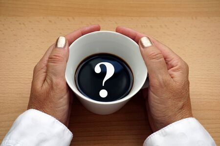 White question mark in a cup of black coffee on a wooden background hold it by the hands of a middle aged woman. Concept image with copy space