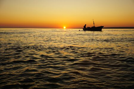 Black silhouette of fisherman in the fishing boat at orange sunset on the seacoast Stockfoto