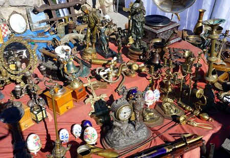 Antique stuff and worthless old products for sales on the market, exposed on the table in the street on the sunny day Stock Photo