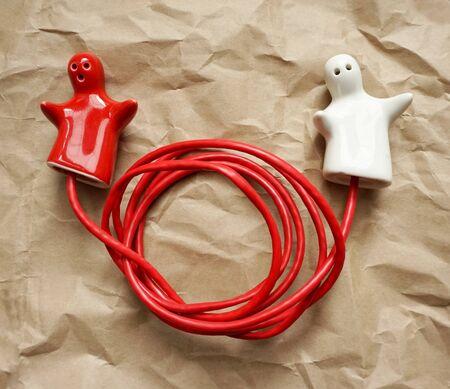 Konzeptioneller Hintergrund mit Verbindung oder Trennung als Konzept. Ein Paar rot-weiße Keramikfiguren, die mit dem roten Draht verbunden sind