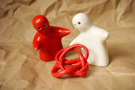 Tangled red wire between two ceramic figurines as humans with free copy space Stock Photo