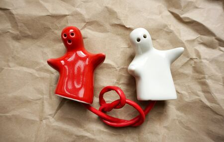 Pair of two red and white porcelain figurines in the form of people tied to a red wire tied into a knot