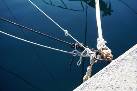 Knots of ropes above the blue sea surface and metal hoops used to tie ships or boats in the marine