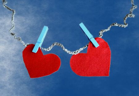 Two red hearts made of red soft cloth attached with clothespin clips and hung on a ribbon of natural rope on a blue background like the sky. Concept love background for Valentine day with copy space Foto de archivo - 138047795