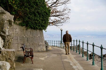 A lonely elderly man walking alone on a promenade by the sea on a gloomy and cloudy day. A man walks in an environment of healthy nature and clean sea air