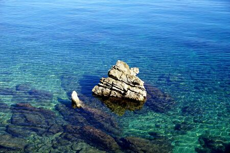 Big rocky stone in the middle of clear shallow sea water in the beautiful blue and turquoise lagoon on a sunny day. Marine unpolluted environment background