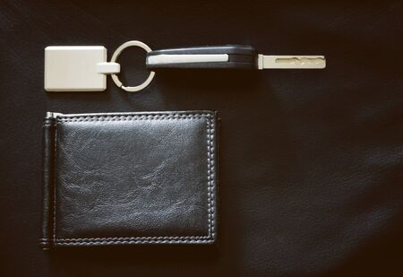 Car key with pendant and black wallet laid on black leather background Фото со стока