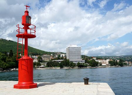 Red metal lighthouse in the port of Opatija town and a view of the Ambassador hotel Standard-Bild