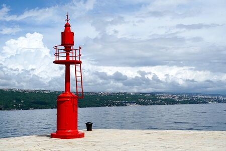 Lighthouse on the waterfront in port of Opatija and view to the city of Rijeka in Croatia