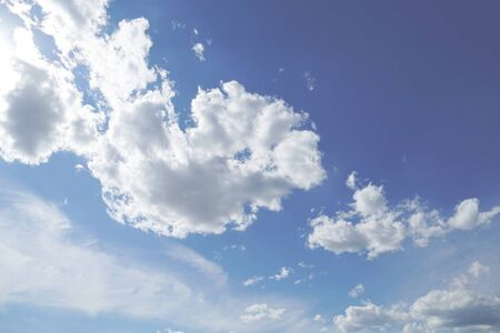 Veiled foggy cumulus clouds floating in the blue sky after summer rainfall