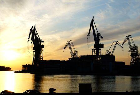 Black silhouette of a shipyard cranes on the seashore at dusk Standard-Bild