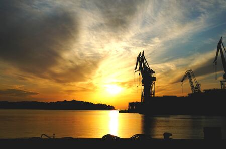 Industrial background versus nature background. Silhouettes of cranes in the shipyard against the beautiful orange color sunset on the seashore