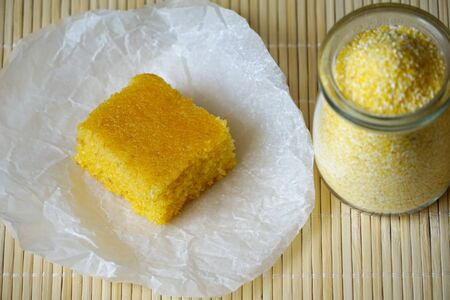 Piece of tasty delicious homemade sweet cornbread, top view with jar full of cornmeal Standard-Bild