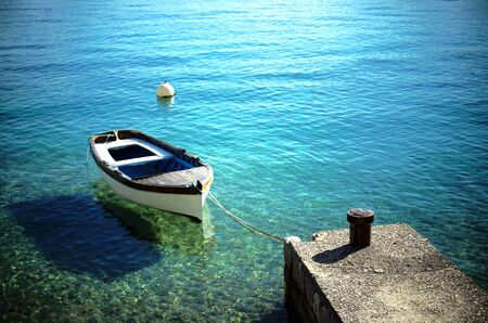 Scenic view of stone pier with mooring rowboat on beautiful blue and turquoise color of sea