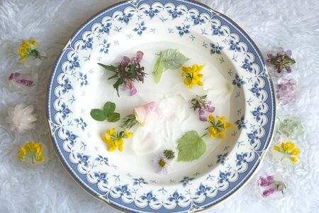 Fresh beauty routine with ice cold water and spring flowers in it, top view
