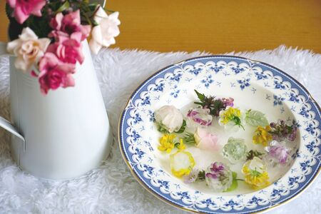 Beauty and skin care concept. Natural cosmetics and care with flowers and ice cubes in fresh water for beauty routine