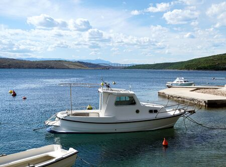 Boats in a small picturesque harbor in front of the bridge to the island of Krk in Croatia